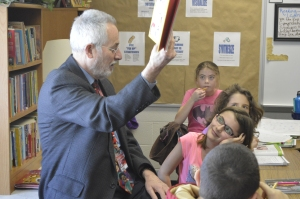 Mike's granddaughter Zoe beams with pride as he reads to her class